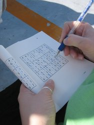 person solving sudoku in a book